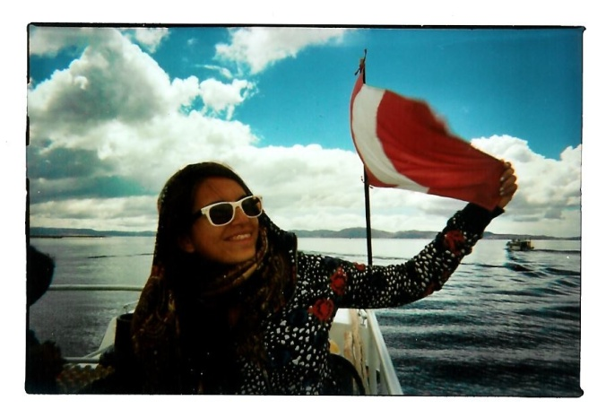Image Credit: Lieselotte Reunbrouck. Belinda with a Peruvian flag at Lake Tititcaca. Talk about finding roots.